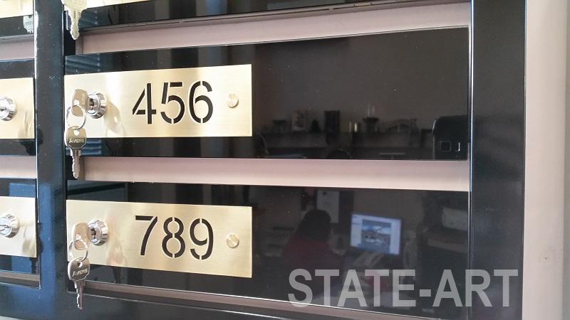 Фасад дверки почтовой ячейки из черного стекла лакобель и латунной шлифованной номерной накладки